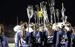 The girls' lacrosse team huddles during their game against Corner Canyon.