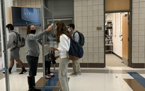Administration checking student's temperature in the morning before the day begins.