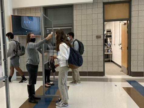 Administration checking students temperature in the morning before the day begins.