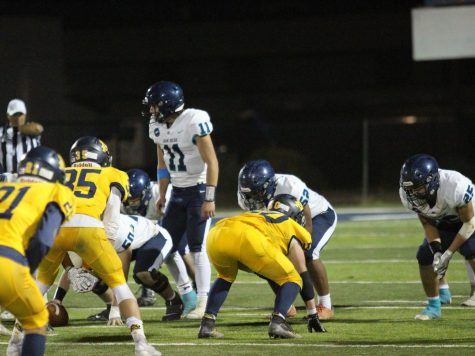 JDCHS football lines up against Summit Academy as Junior Tyler Easter prepares to receive the ball.