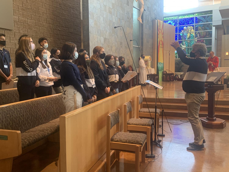 John VanWagoner directing the choir at the Junior Class Mass last Thursday.